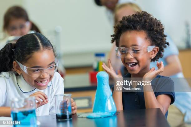 Excited African American schoolgirls enjoy science experiment