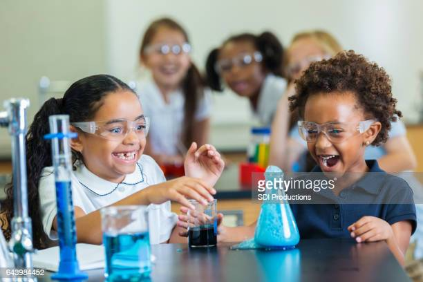 Excited African American schoolgirls participate in chemistry experiment
