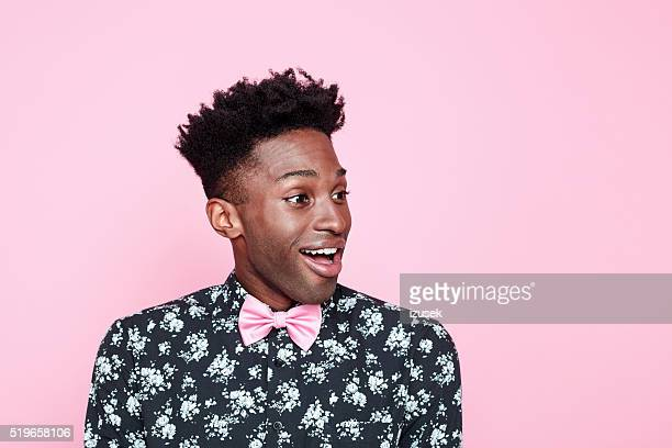 Excited afro american guy against pink background