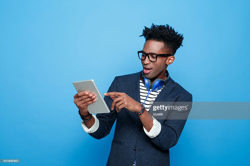 Excited afro american guy in fashionable outfit, holding digital tablet : Stock Photo