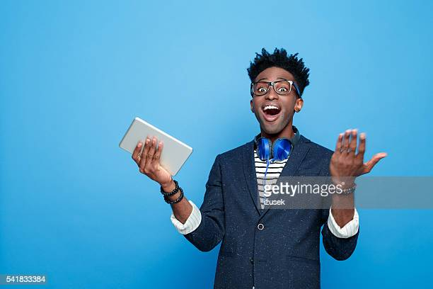 excited afro american guy in fashionable outfit, holding digital tablet - nerd stock pictures, royalty-free photos & images
