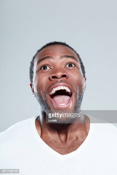excited afro american man looking away and laughing - mouth open stock pictures, royalty-free photos & images
