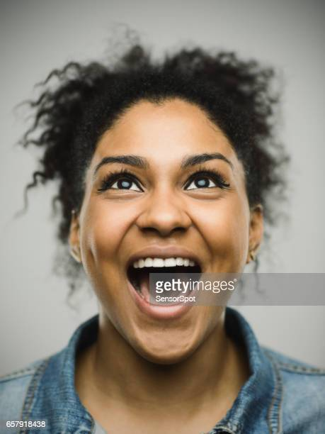 excited afro american woman shouting against gray background - cantare foto e immagini stock