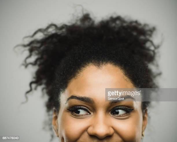 Excited afro american woman smiling against gray background
