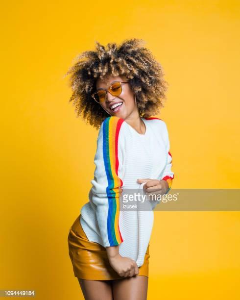 animado garota afro dança contra fundo amarelo - funky - fotografias e filmes do acervo