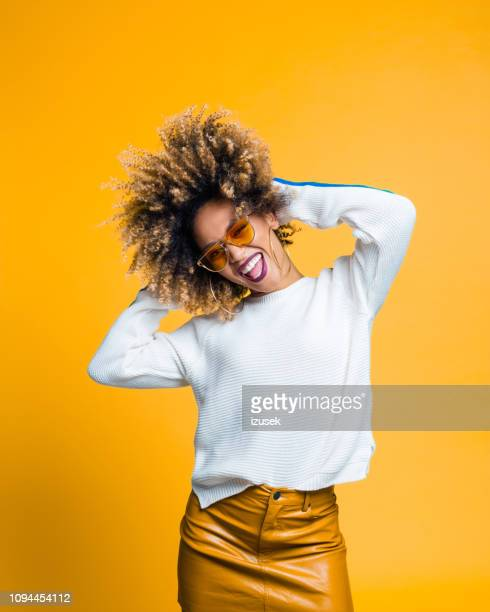 excited afro young woman dancing against yellow background - afro stock pictures, royalty-free photos & images