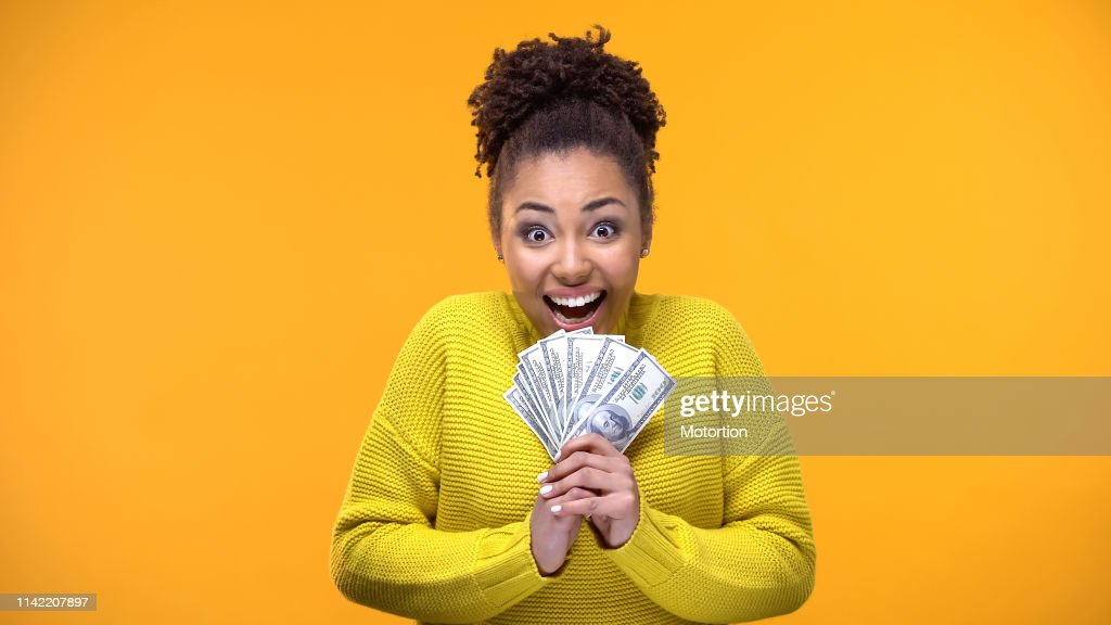 Excited Afro-American woman holding bunch of dollars, lottery winner, fortune : Stock Photo