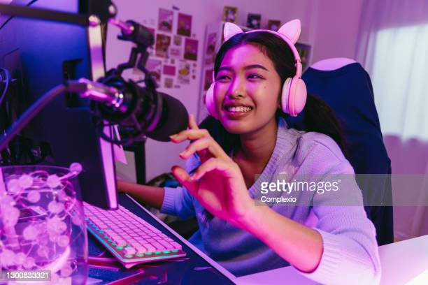 excited and smiling gamer girl in cute headset with mic playing an online video game. young asian woman talking to players and audience on personal computer at home - gamer stock pictures, royalty-free photos & images