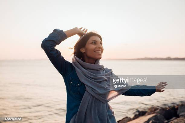 excited arab girl raising her arms and enjoying by the sea - women's issues stock pictures, royalty-free photos & images