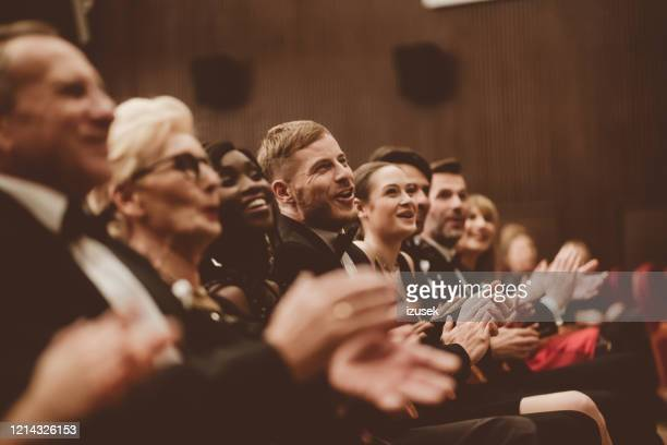 excited audience clapping in the theater - awards ceremony stock pictures, royalty-free photos & images
