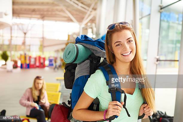 Excited backpacker smiles to camera