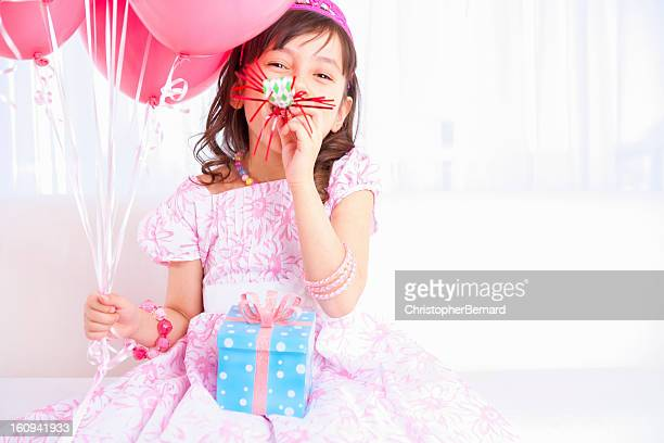 excited birthday girl playing with a party horn blower - birthday balloons stock photos and pictures