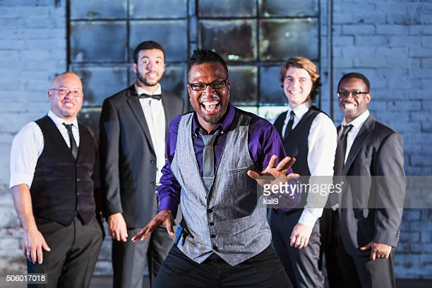 Excited black man laughing, standing in front of group