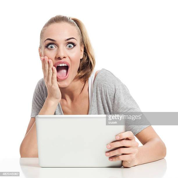 Excited blond hair young woman using digital tablet