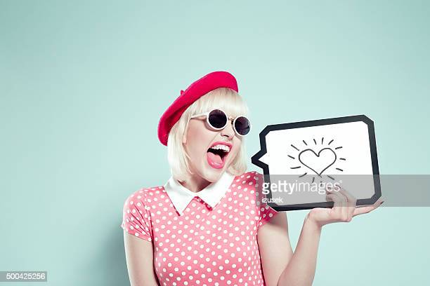 Excited blonde young woman holding speech bubble with drawn heart