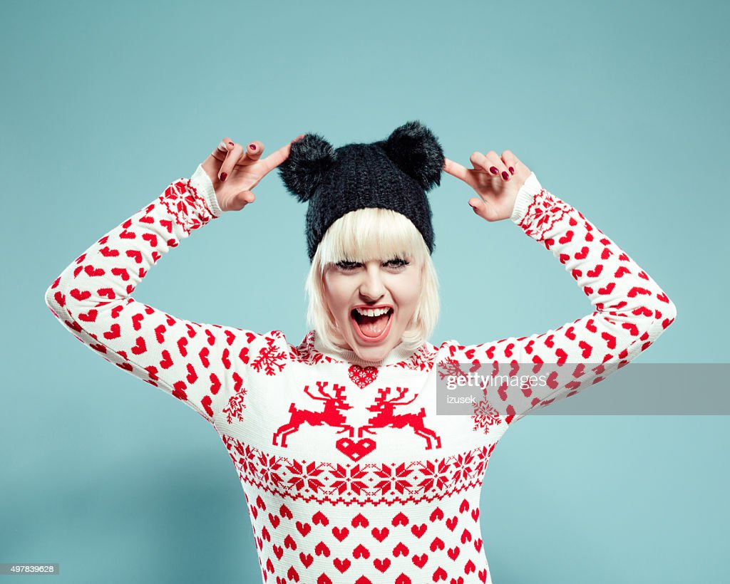 Excited blonde young woman wearing xmas sweater and bobble hat : Stock Photo