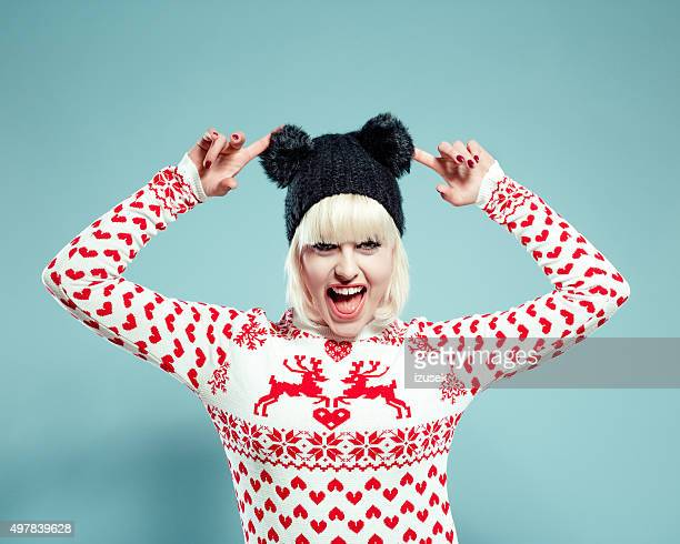 Excited blonde young woman wearing xmas sweater and bobble hat