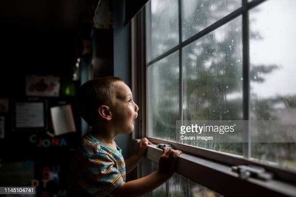 excited boy looking out a window with raindrops at a stormy sky - rain stock-fotos und bilder
