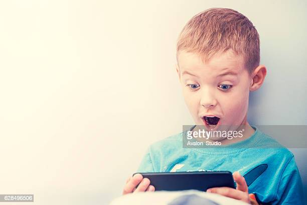 excited boy playing with a smartphone. - ecstatic stock photos and pictures