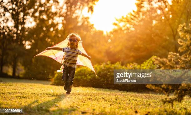 excited boy running in park with flying dragon on his back - kite stock pictures, royalty-free photos & images