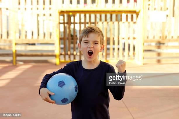 Excited Boy Screaming While Holding Soccer Ball