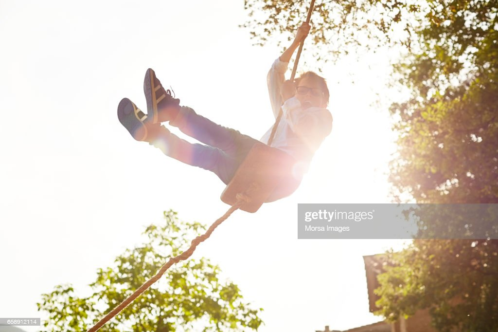 Excited boy swinging at back yard on sunny day : Stock Photo