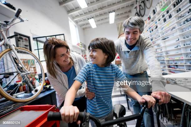 Begeistert junge mit seinem neuen Fahrrad im Fahrradladen und seine Eltern neben ihm auf der Suche sehr zufrieden