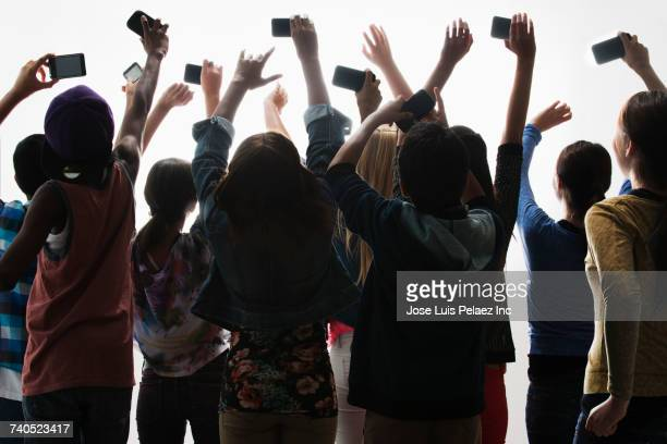 Excited boys and girls with arms raised photographing with cell phones
