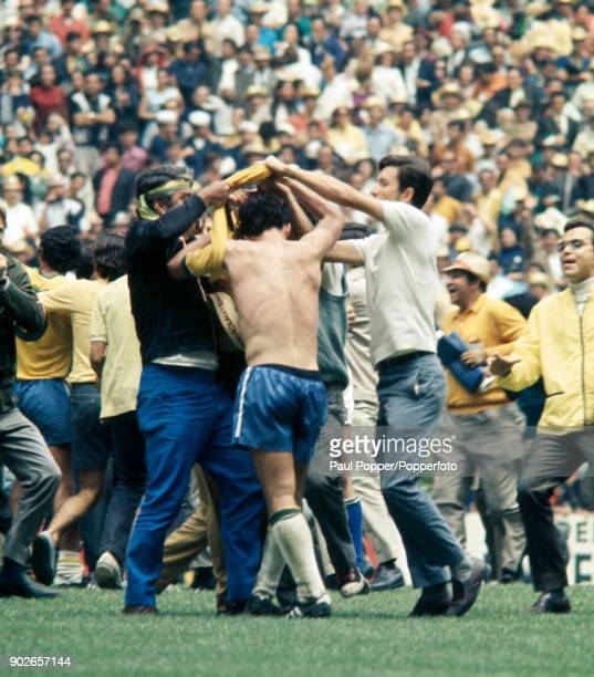 Excited Brazilians surround Tostao who is then stripped by fans seeking souvenirs following the FIFA World Cup Final between Brazil and Italy at the...
