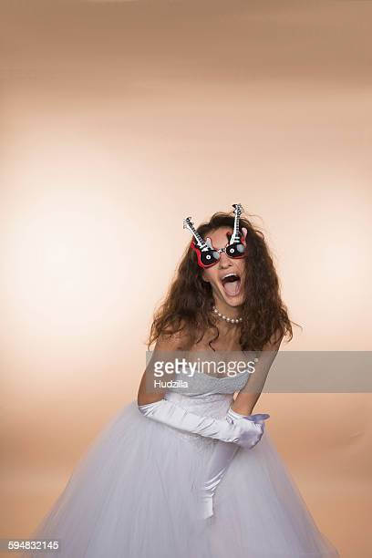Excited bride in guitar shaped glasses screaming against colored background