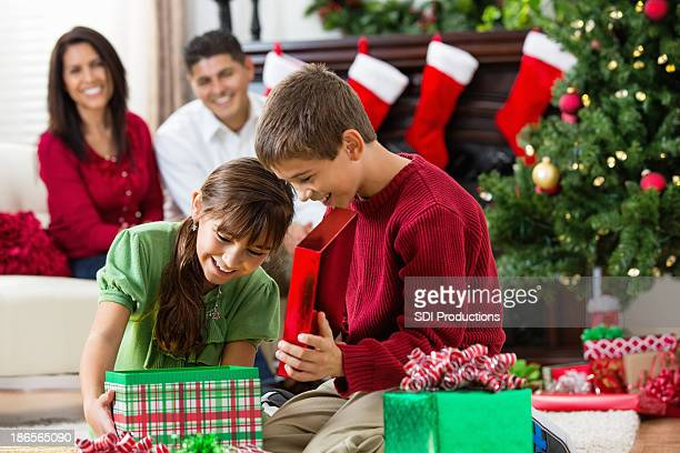Excited brother and sister opening gift on Christmas morning