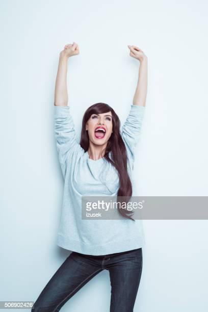 heureux brunette en tenue décontractée, en soulevant les bras et en train de crier - libre de droit photos et images de collection