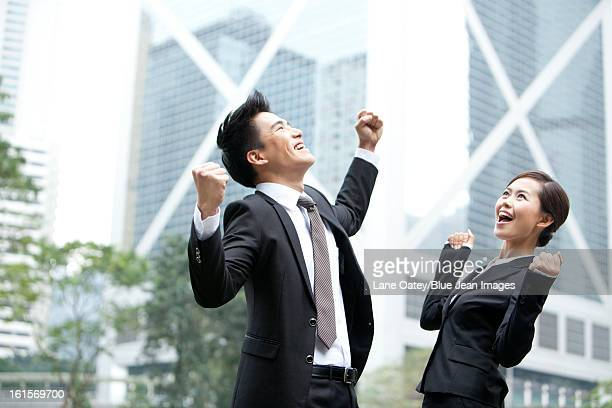 excited business colleagues punching the air outdoors, hong kong - ガッツポーズ ストックフォトと画像