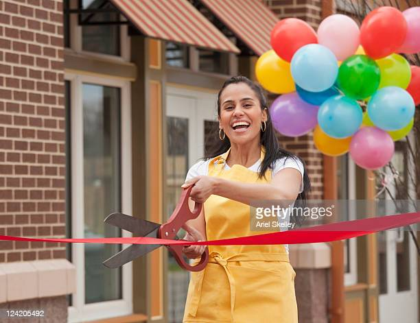 excited business owner cutting ribbon on grand opening - evento de abertura - fotografias e filmes do acervo