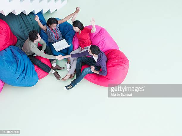 Excited business people with arms raised sitting in bean bag chairs and looking at laptop