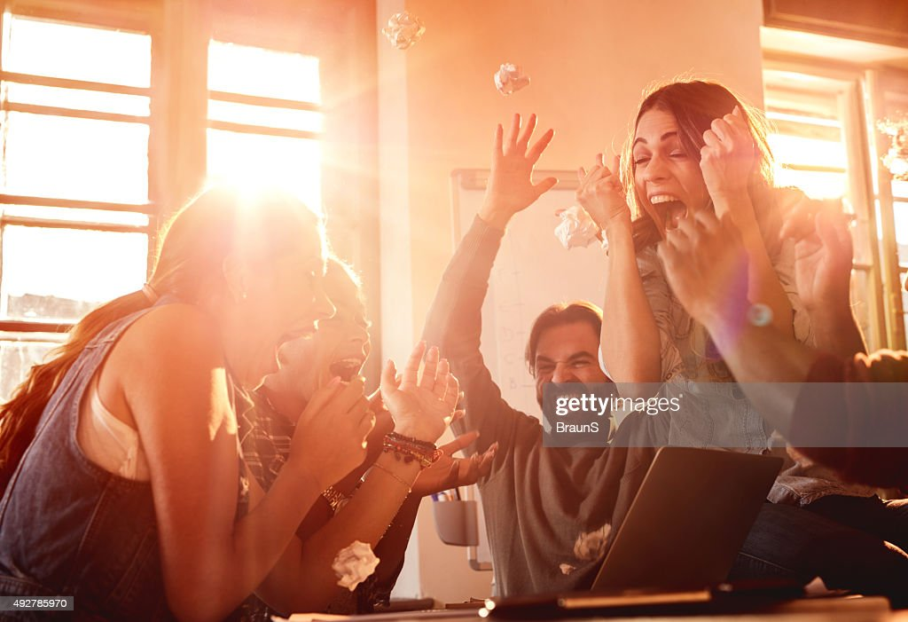 Excited business team celebrating their success at office. : Stock Photo