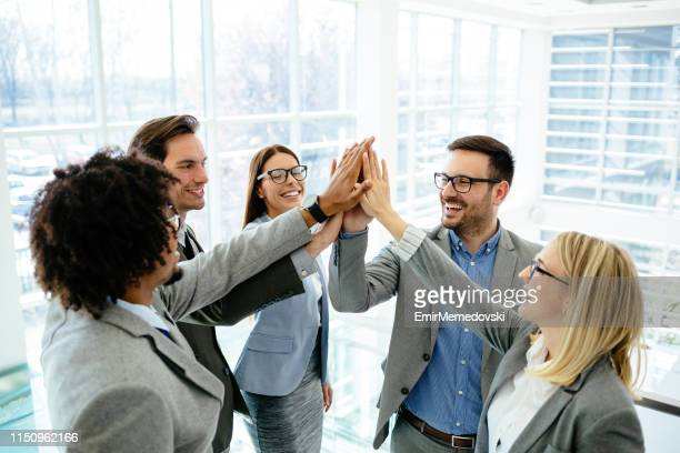 excited business team give high five celebrate corporate success - società foto e immagini stock