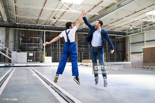 excited businessman and worker jumping and high fiving in a factory - high five stock-fotos und bilder