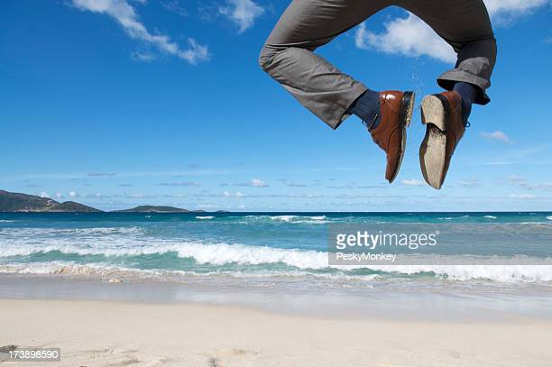 Excited Businessman Celebrates Clicking His Heels Above Tropical Beach