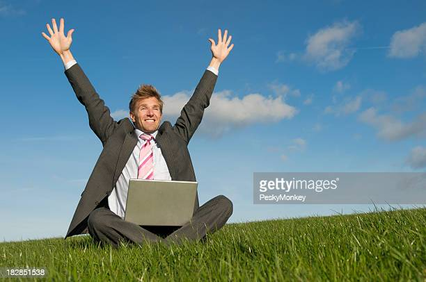 Excited Businessman Celebrating in Meadow Throwing Arms to the Air