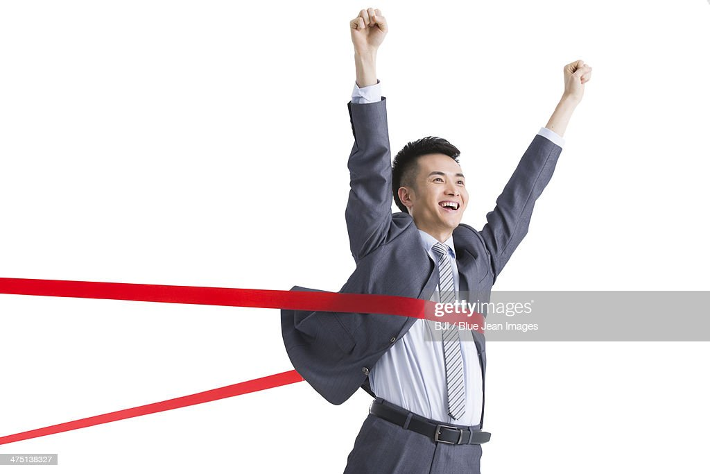 Excited businessman crossing the finish line : Stock Photo