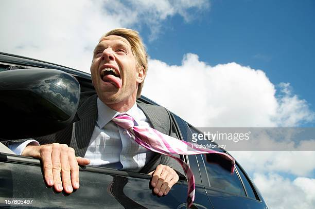 Excited Businessman Hangs out the Car Window