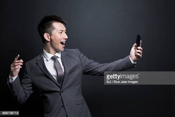 Excited businessman holding a smart phone