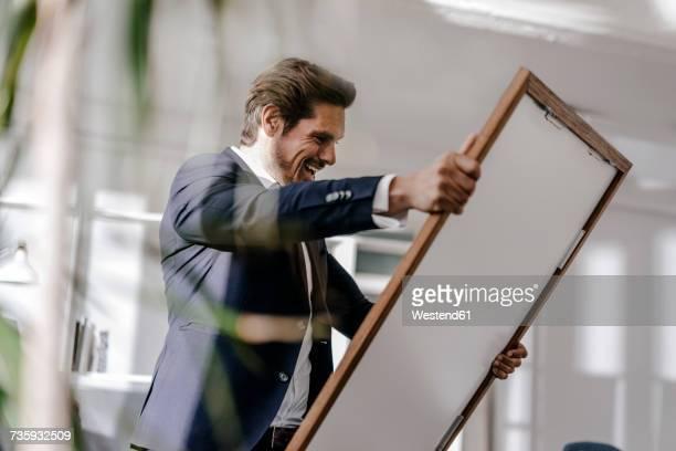 excited businessman holding picture frame - kunsthändler stock-fotos und bilder