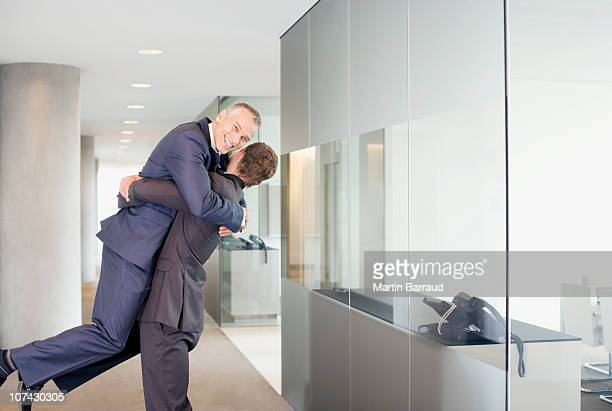 excited businessman lifting co-worker in office corridor - omarmd stockfoto's en -beelden
