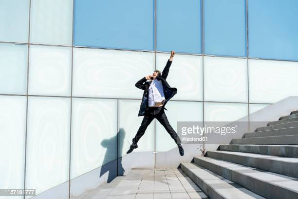 excited businessman on cell phone jumping in the city - begeisterung stock-fotos und bilder