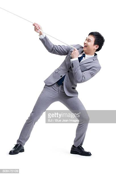 Excited businessman pulling rope
