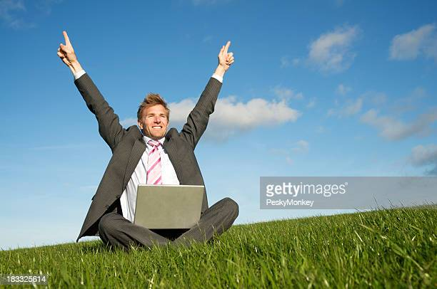 Excited Businessman Using Laptop Pointing His Fingers to the Sky