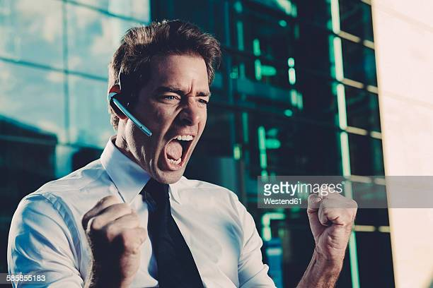 Excited businessman with clenched fists screaming outside office building