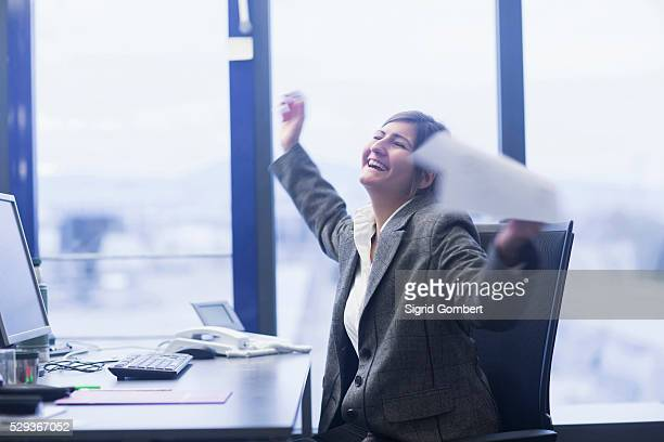 excited businesswoman celebrating her success in an office, freiburg im breisgau, baden-w��rttemberg, germany - sigrid gombert stock pictures, royalty-free photos & images